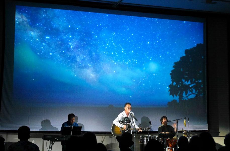 石垣島在住の写真家、天の川次郎氏撮影の動画や写真をバックスクリーンに大きく投影。