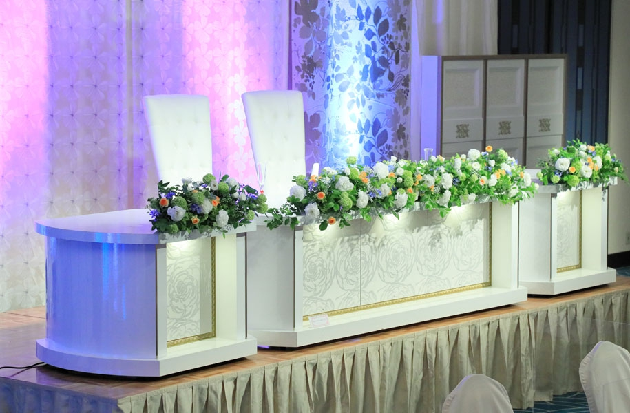 【大宴会場披露宴メイン席イメージ】舞台の向かい側に設置されるメイン席。セレモニーケーキ・アクアイリュージョンとともに装花イメージをご覧いただきました